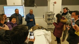 A Visiting Scholar from China photographs a dummy patient in a simulation lab at Howard University's College of Medicine.
