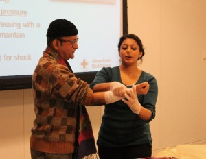 Fulbright Scholar Romain Maitra from India volunteers to play the role of victim, while American Red Cross instructor, Lipica Shah, demonstrates how to stop heavy bleeding from a deep wound.