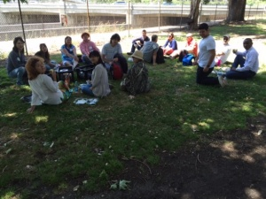 Scholars enjoy a picnic lunch in a riverside park.