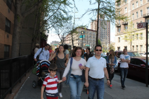 Scholars and their families walking down 116th Street in Harlem